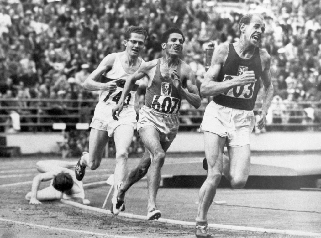 """FILE - In this July 24, 1952, file photo, British athlete Christopher """"Chris"""" Chataway falls as Emil Zatopek of Czechoslovakia, followed by Alain Mimo..."""