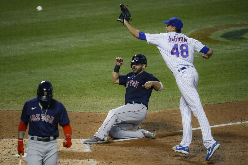Boston Red Sox'S Mitch Moreland, center, scores on a wild pitch by New York Mets' Jacob deGrom (48) during the fourth inning of a baseball game Wednes...