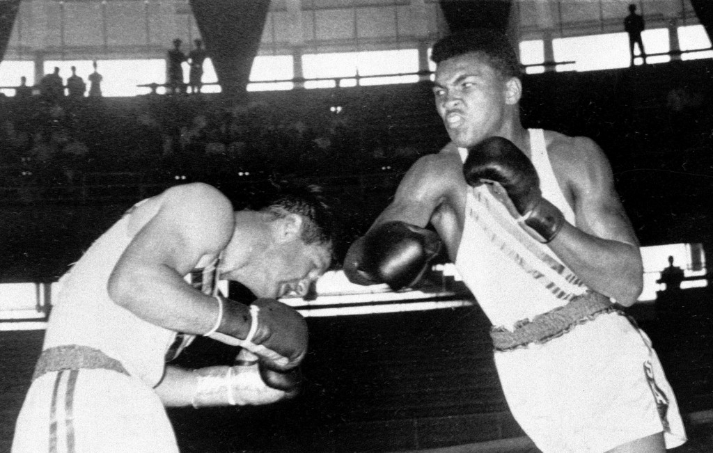 FILE - In this Sept. 3, 1960, file photo, Cassius Clay, 18-year-old from Louisville, Ky., throws a right at Tony Madigan of Australia, left, during th...