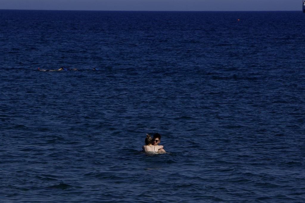 A couple enjoy the sea in southern coastal city of Limassol, Cyprus, on Wednesday, July 29, 2020. Cyprus' Tourism Minister Savvas Perdios says the cou...