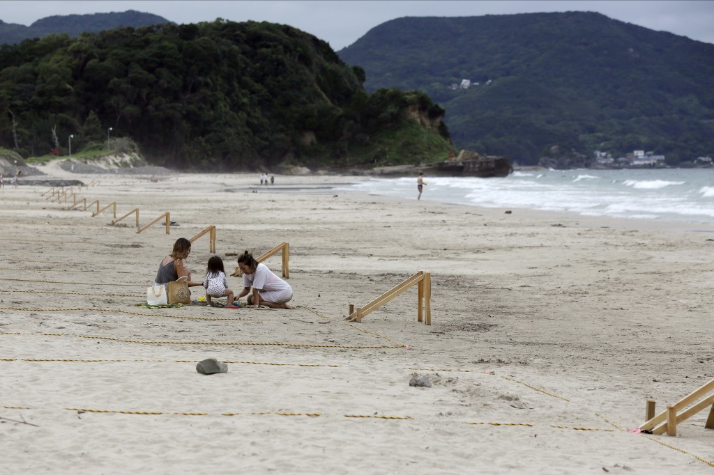 Beach goers stay within a roped off grid as the city of Shimoda tries to maintain social distancing to avoid spreading COVID-19 Thursday, July 30, 202...