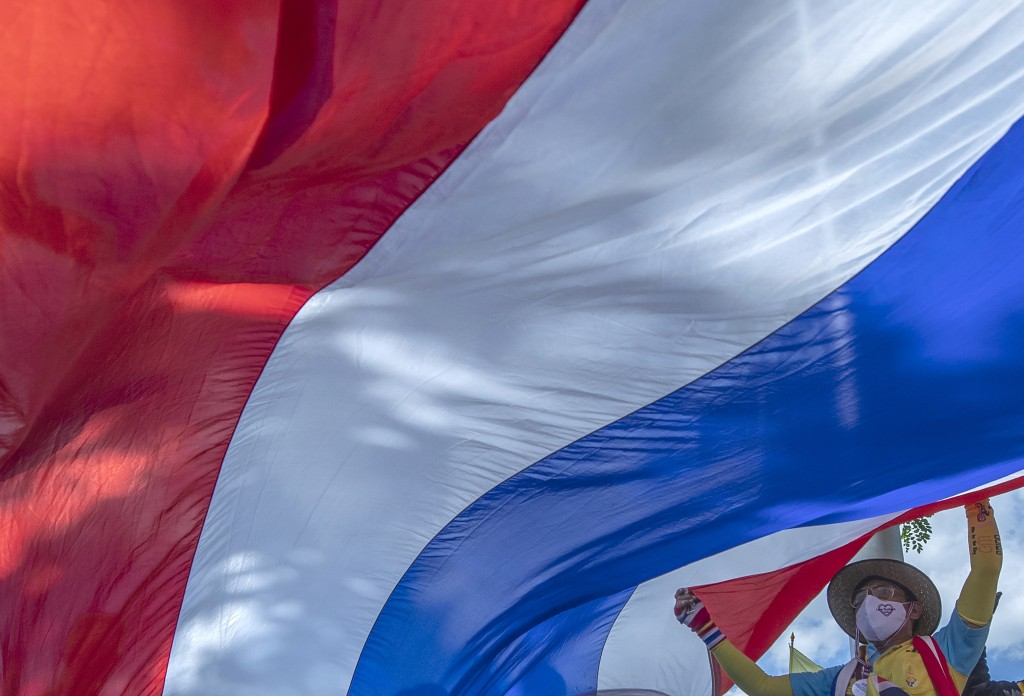 Supporter of Thailand's monarchy lift a giant national flag during a gathering stating their concern over the country's pro-democracy movement which t...