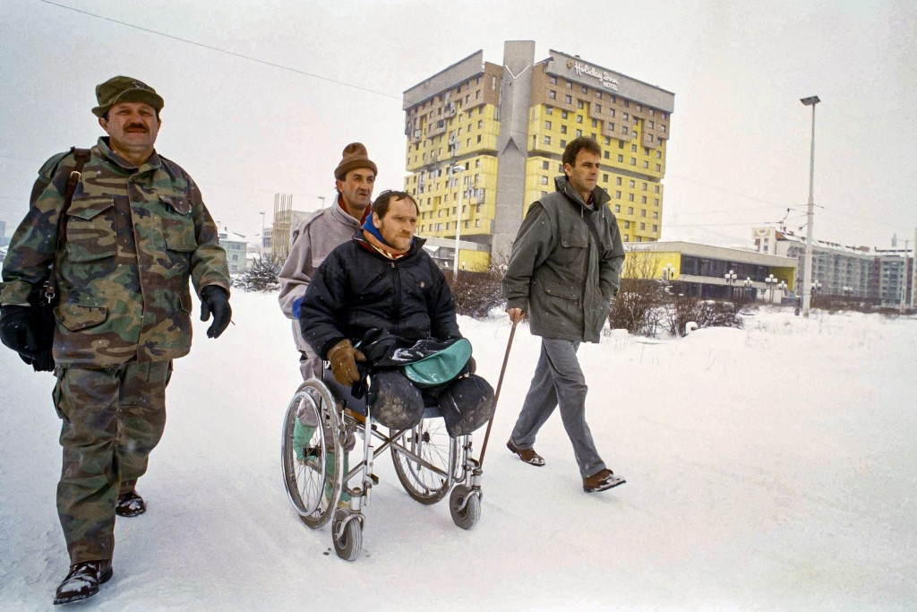FILE - In this Tuesday, Feb. 15, 1994 file photo, three wounded Bosnian war veterans, walking with the aid of artificial limbs and pushing a legless c...