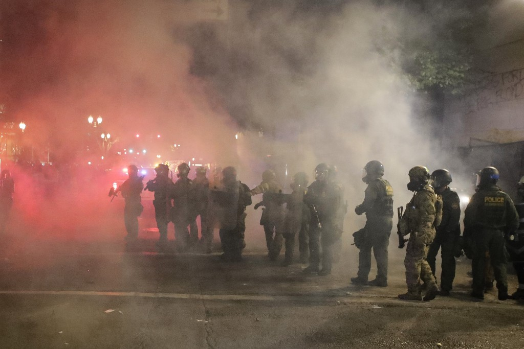 Federal officers walk in formation after a crowd threw fireworks during a Black Lives Matter protest at the Mark O. Hatfield United States Courthouse ...