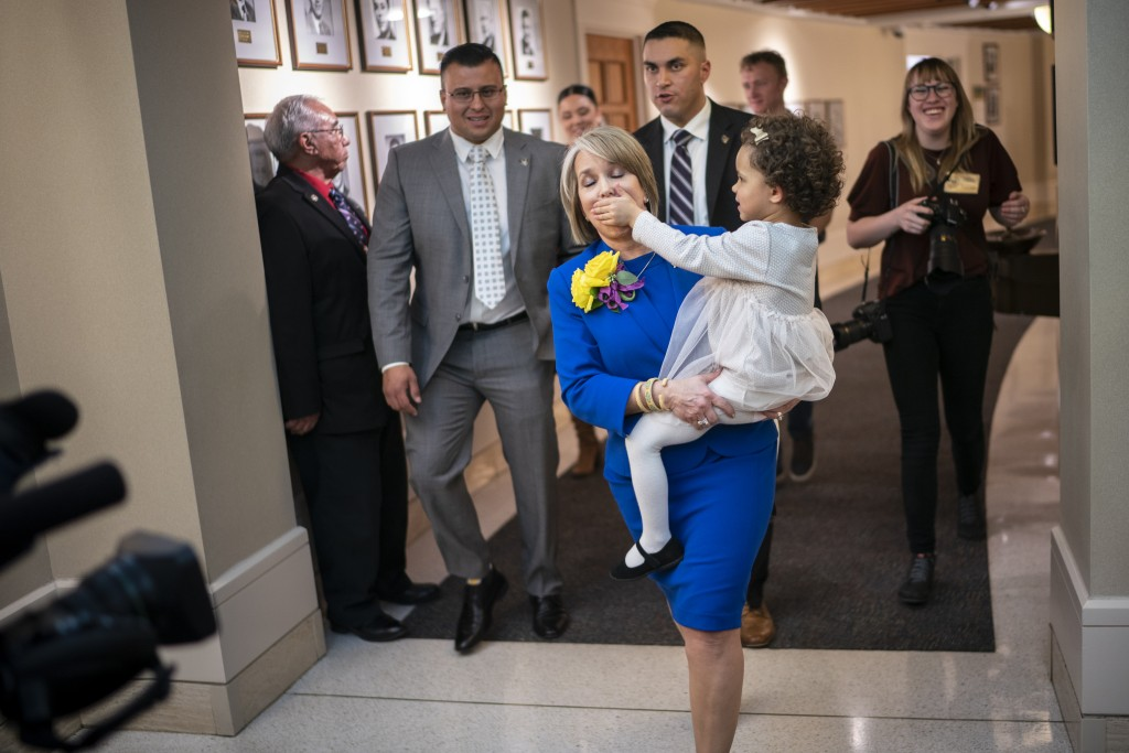 FILE - New Mexico Gov. Michelle Lujan Grisham is silenced by her granddaughter Avery Stewart in this Jan. 21, 2020, file photo while being escorted ou...