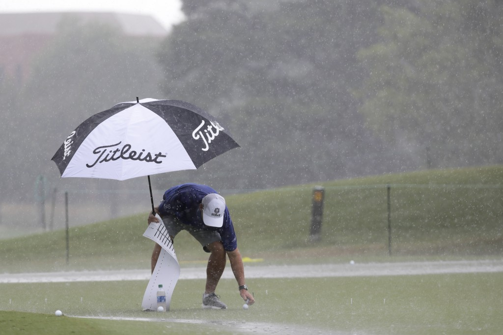 Equipment is picked up off the practice green as rain falls at the World Golf Championship-FedEx St. Jude Invitational Wednesday, July 29, 2020, in Me...