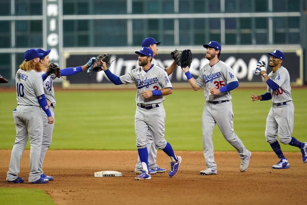 Los Angeles Dodgers' Chris Taylor (3), Cody Bellinger (35) and Mookie Betts (50) celebrate with teammates after a baseball game against the Houston As...