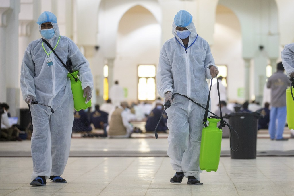 Health officials spray disinfectant inside the Namira Mosque in Arafat during the annual hajj pilgrimage near the holy city of Mecca, Saudi Arabia, Th...