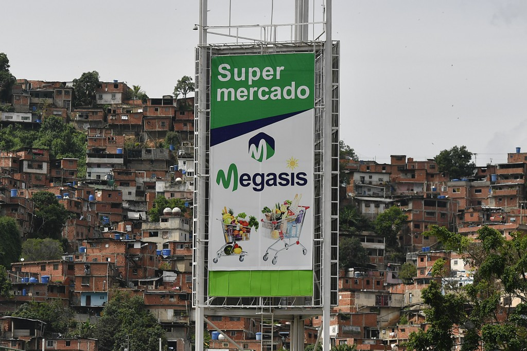 A sign for the first Iranian supermarket that is set to open its doors in Latin America stands near a poor neighborhood in Caracas, Venezuela, Wednesd...