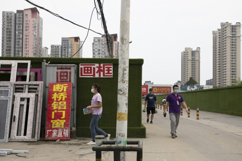 Residents wear masks as they go about their daily lives in Beijing, Thursday, July 30, 2020. China is stepping up testing for COVID-19 in an attempt t...