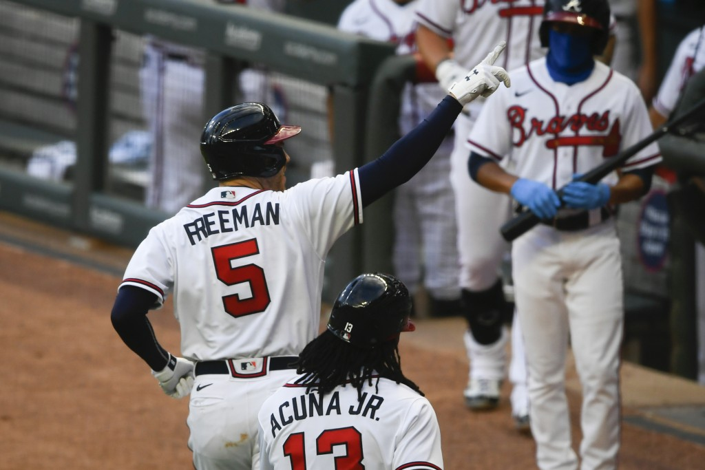 Atlanta Braves' Freddie Freeman (5) celebrates as he motions to empty seats after hitting a two-run home run during the third inning of the team's bas...