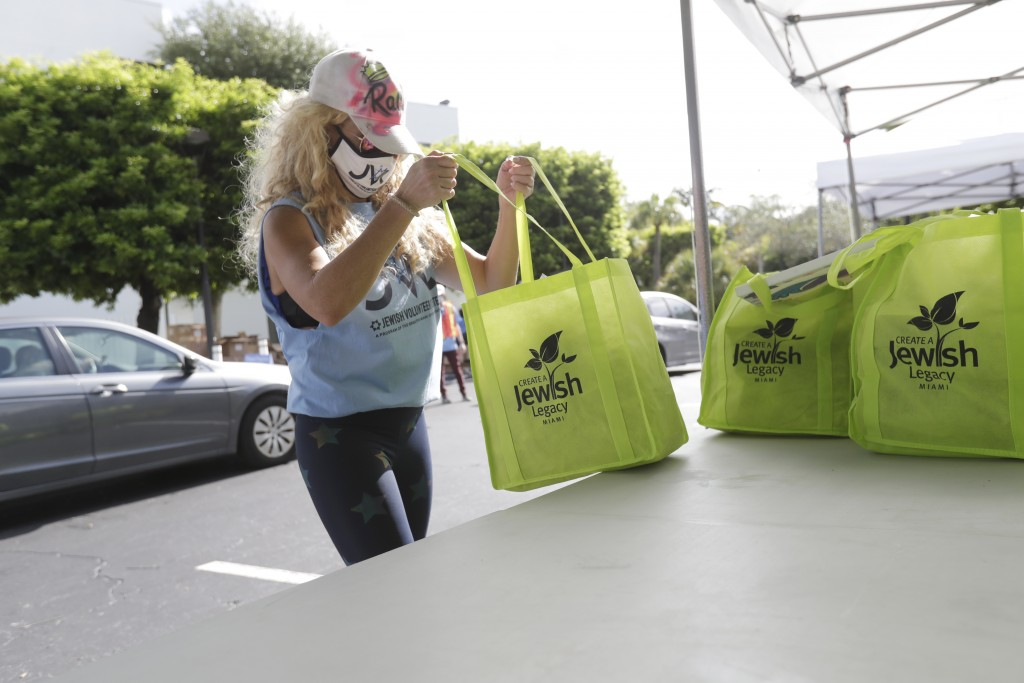 Volunteer Rachel Friedland prepares to load food in a car at a kosher food drive-thru distribution site, Wednesday, July 29, 2020, at the Greater Miam...