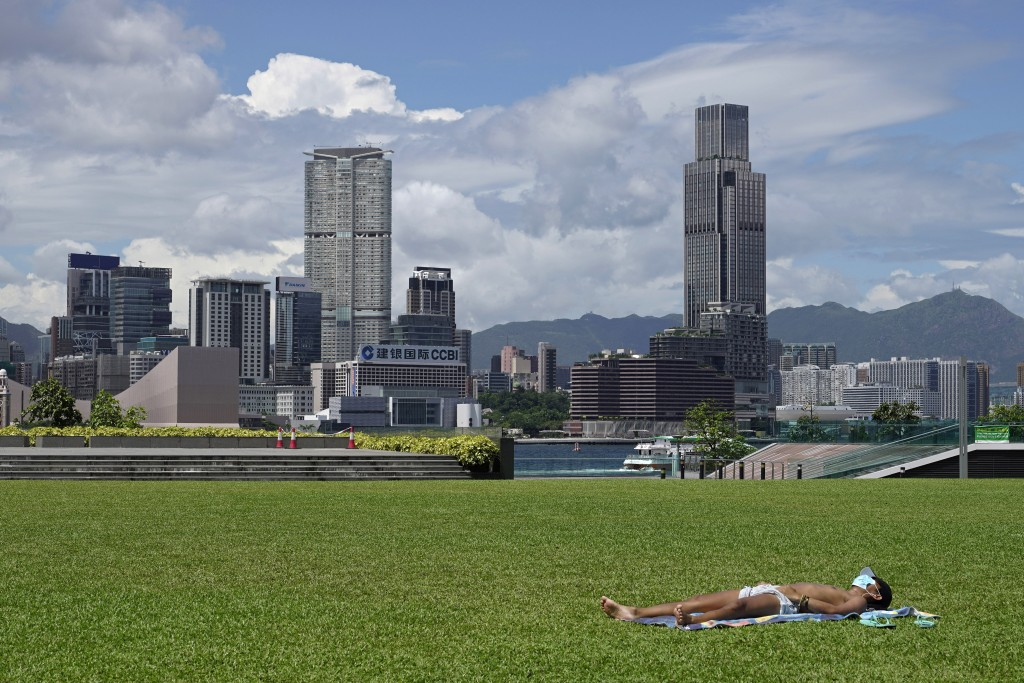 A man sunbathes at a park in Hong Kong Thursday, July 30, 2020. As of Wednesday, Hong Kong reported over 3,000 coronavirus infections, with dozens of ...