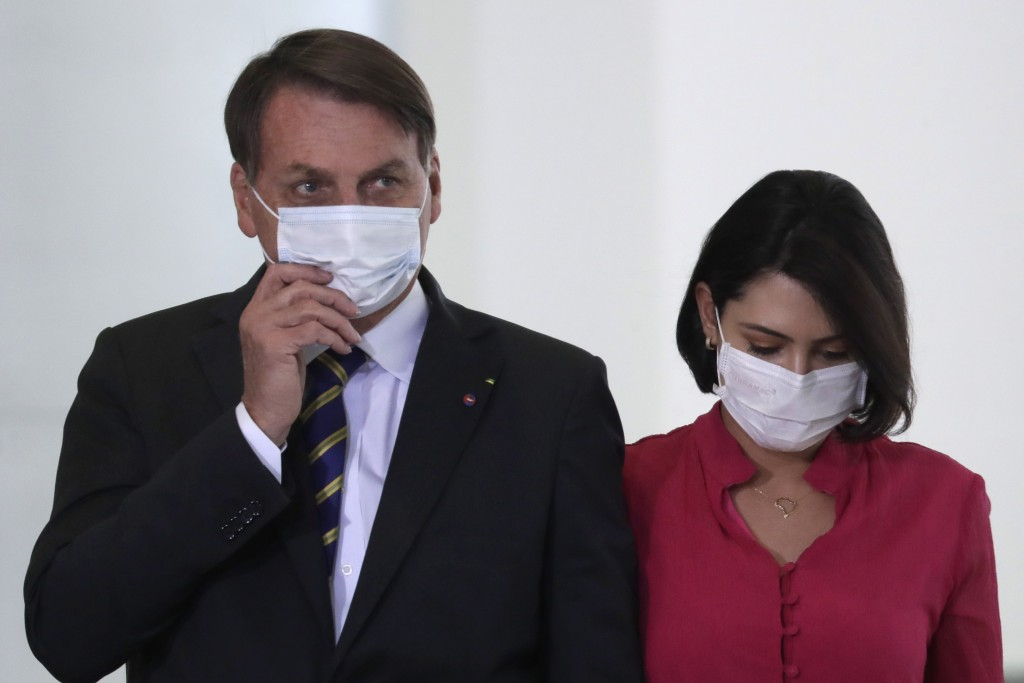 Wearing masks to curb the spread of the new coronavirus, Brazil's President Jair Bolsonaro and his wife Michelle Bolsonaro, arrive to attend the launc...