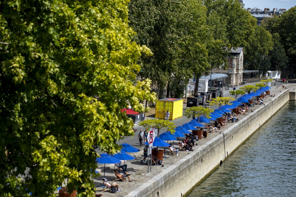 FILE - In this July 28, 2020, file photo, people enjoy the sun on deckchairs along the river Seine in Paris. An outbreak among 18- to 25-year-olds at ...