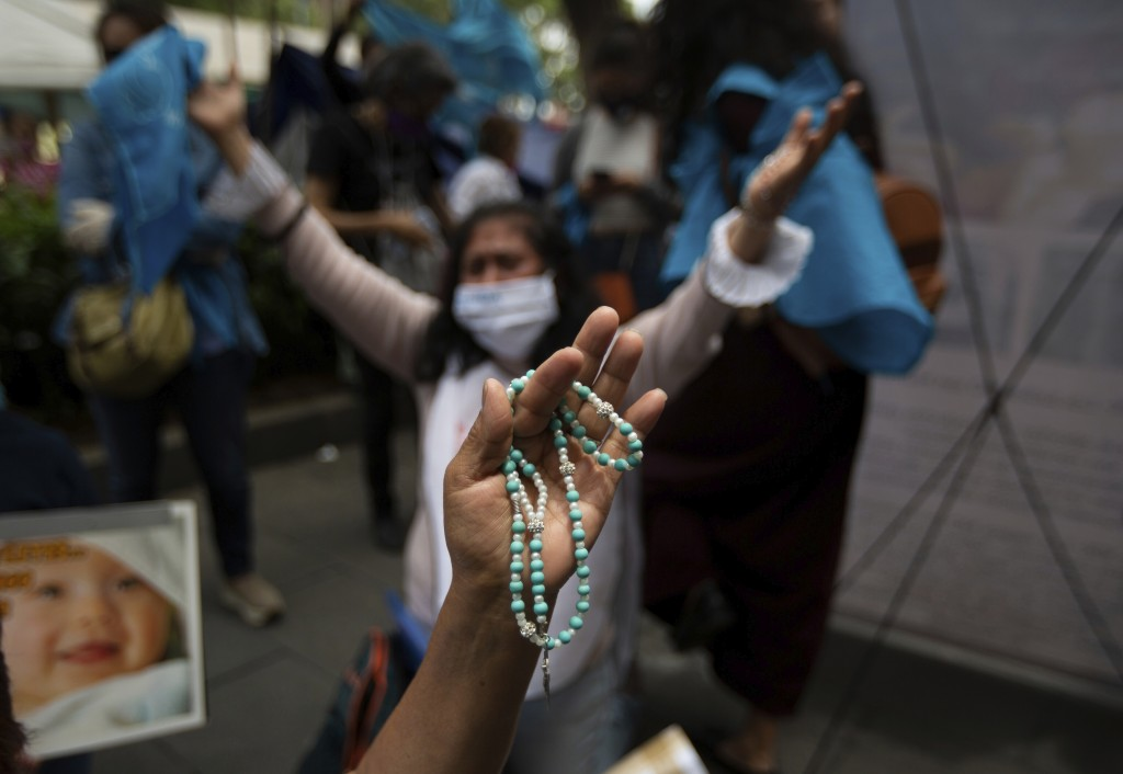 A woman clutches a rosary as she celebrates the Supreme Court's decision against an injunction in Veracruz state that aimed to decriminalize abortion ...