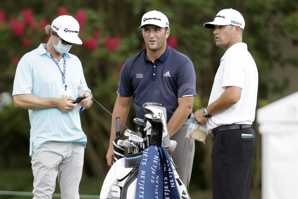 Jon Rahm, of Spain, center, waits on the practice green at the World Golf Championships-FedEx St. Jude Invitational Wednesday, July 29, 2020, in Memph...