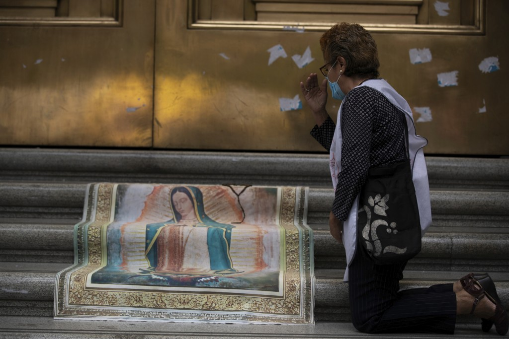 An activist against abortion makes the sign of the cross as she places an image of Our Lady of Guadalupe at the entrance to the Supreme Court to celeb...