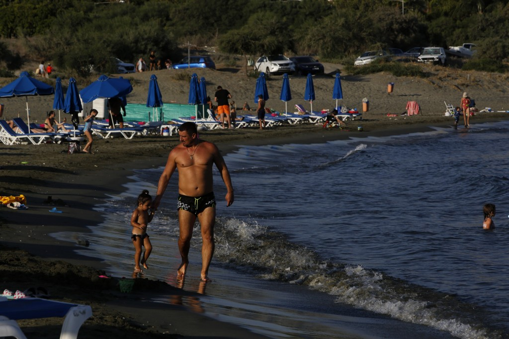 A father with his child walks along Saint Rafael beach in southern coastal city of Limassol, Cyprus, on Wednesday, July 29, 2020. Cyprus' Tourism Mini...