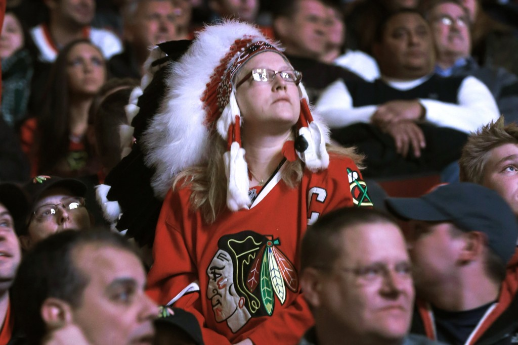 FILE - In this Feb. 19, 2013, file photo, Chicago Blackhawks fan Joy Bereckis  watches a Blackhawk video before an NHL hockey game between the Blackha...