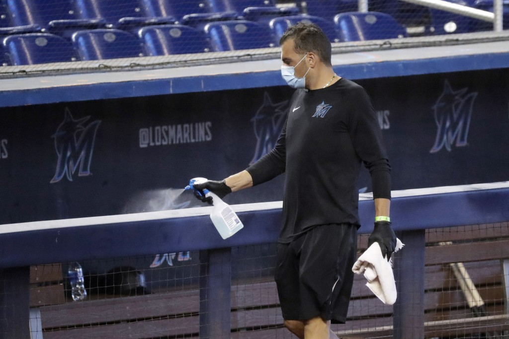 FILE - In this Thursday, July 16, 2020, file photo, a worker sprays the dugout rail to help prevent the spread of the coronavirus, before the Miami Ma...