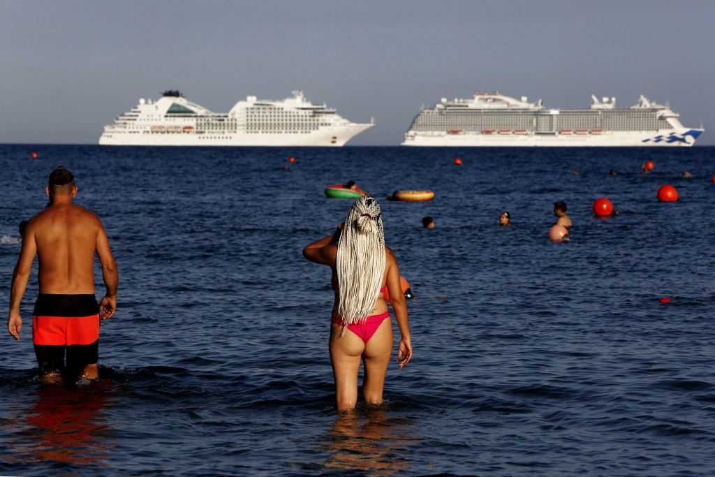 People visit Saint Rafael beach where a number of cruise ships are anchored for refueling and resupply, in southern coastal city of Limassol, Cyprus, ...