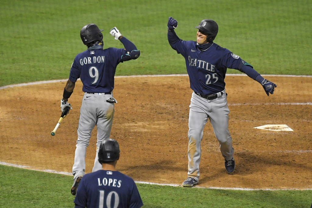 Seattle Mariners' Dylan Moore, right, is congratulated by Dee Gordon, left, after hitting a three-run home run as Tim Lopes watches during the sixth i...