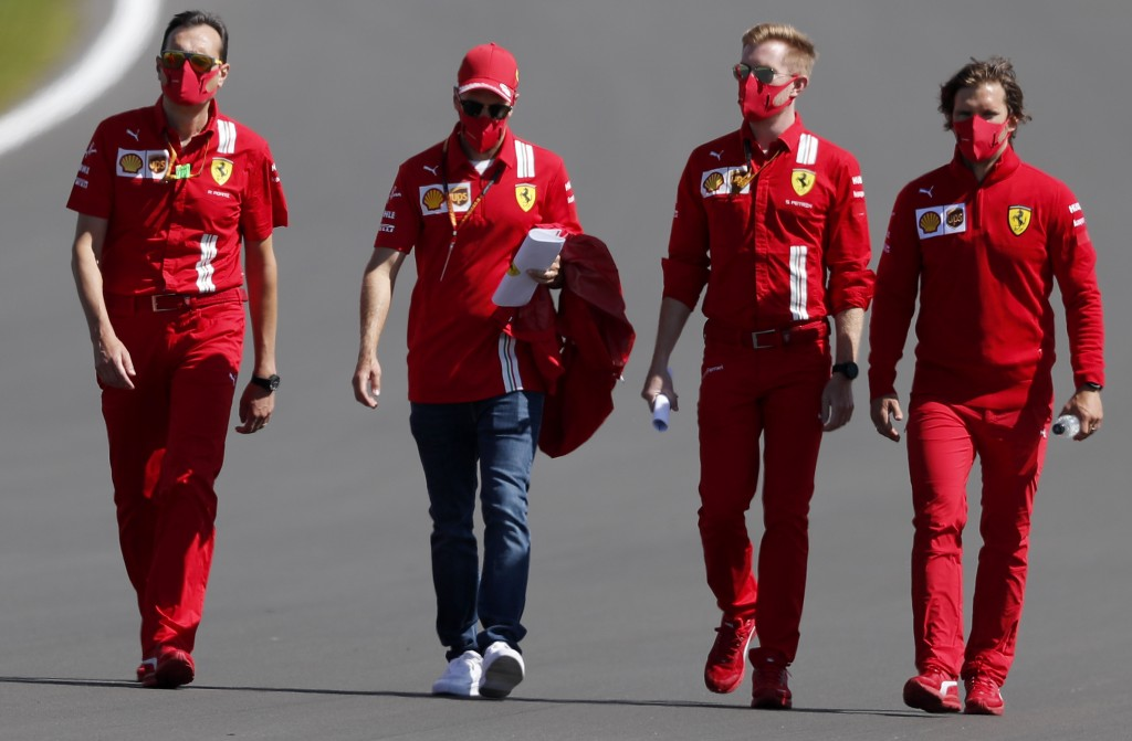 Ferrari driver Sebastian Vettel of Germany, third from right, inspects the track with team members ahead of the British Formula One Grand Prix at Silv...