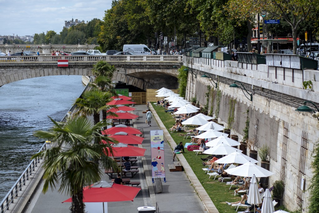 FILE - In this  July 28, 2020, file photo, people enjoy the sun on deckchairs along the river Seine in Paris. An outbreak among 18- to 25-year-olds at...