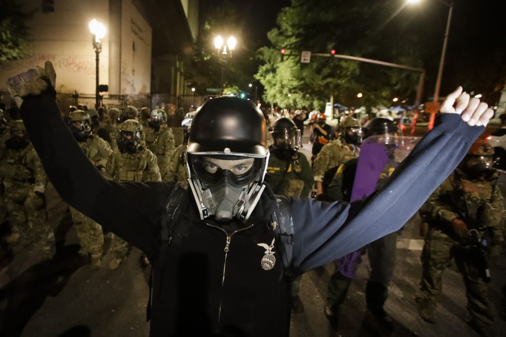 A demonstrator raises his arms in front of federal officers during a Black Lives Matter protest at the Mark O. Hatfield United States Courthouse Wedne...