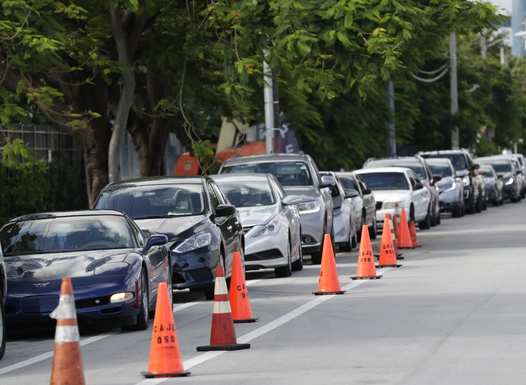 A line of cars wait at the entrance to a kosher food drive-thru distribution site, Wednesday, July 29, 2020, at the Greater Miami Jewish Federation bu...