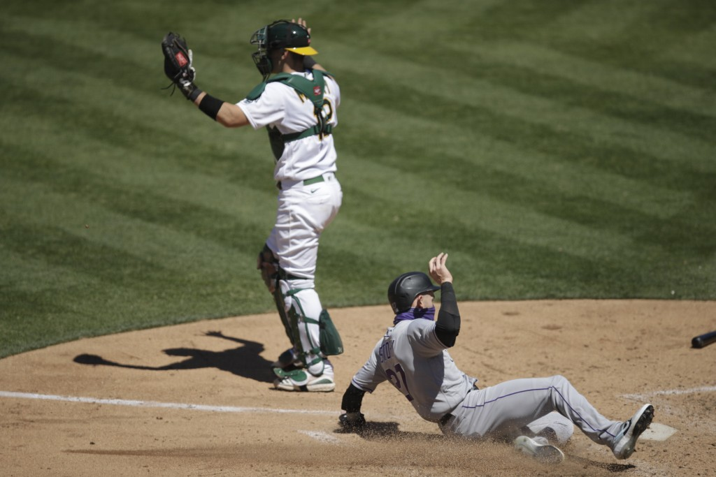 Colorado Rockies' Trevor Story, right, scores past Oakland Athletics catcher Sean Murphy (12) during the eighth inning of a baseball game, Wednesday, ...