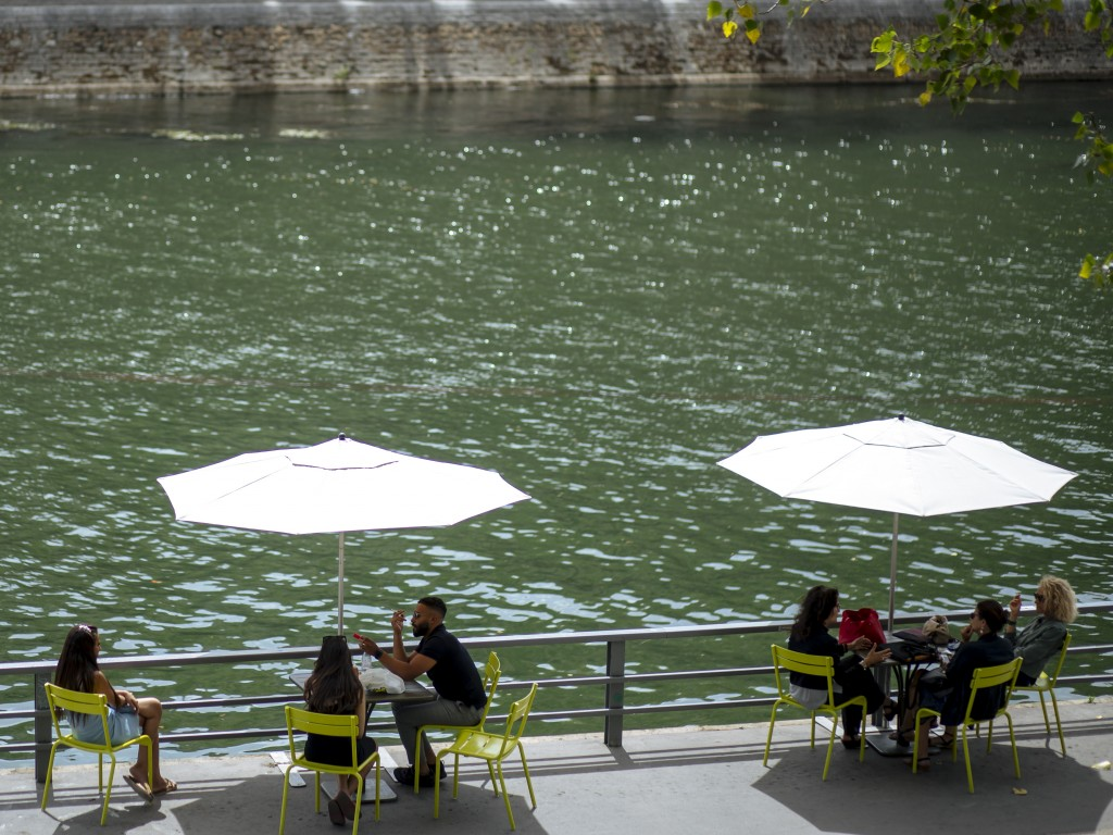 FILE - In this July 28, 2020, file photo, people sit along the river Seine in Paris. An outbreak among 18- to 25-year-olds at a seaside resort on the ...