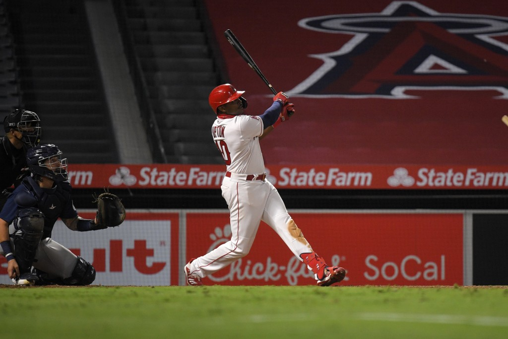 Los Angeles Angels' Justin Upton, right, hits a solo home run as Seattle Mariners catcher Joseph Odom, center, and home plate umpire Edwin Moscoso wat...