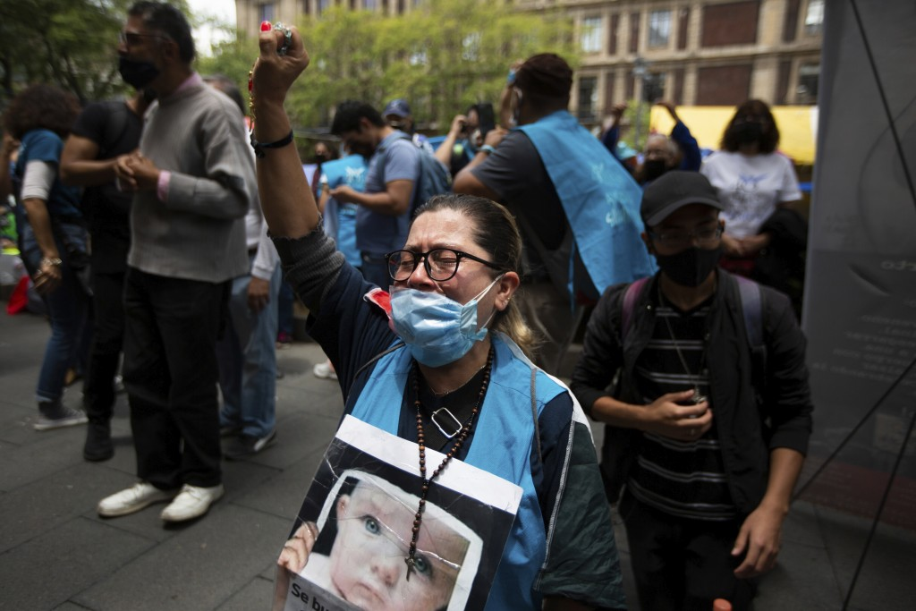 A woman wearing and holding up a rosary celebrates the Supreme Court's decision against an injunction in Veracruz state that aimed to decriminalize ab...