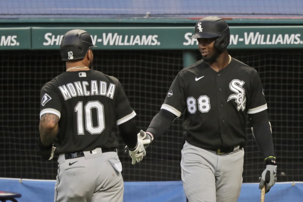 Chicago White Sox's Yoan Moncada (10) is congratulated by Luis Robert (88) after Moncada scored in the ninth inning in a baseball game against the Cle...