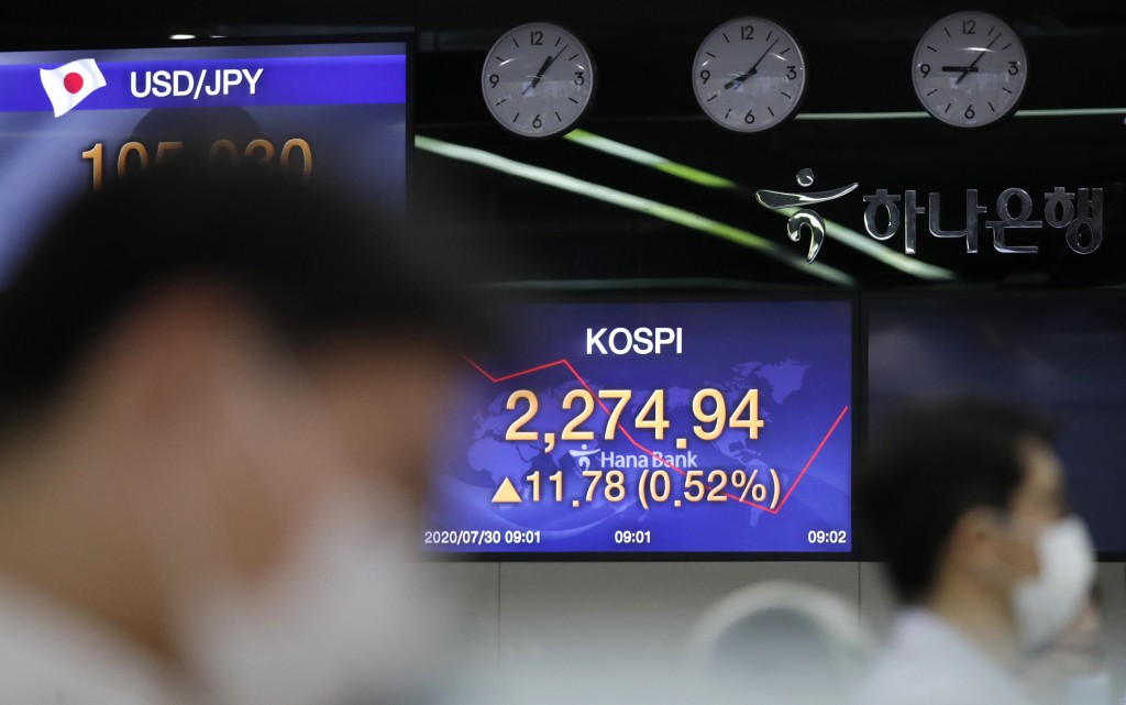 Currency trader watch computer monitors near the screen showing the Korea Composite Stock Price Index (KOSPI) at the foreign exchange dealing room in ...