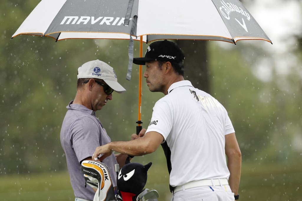 Kevin Na and his caddie try to wait out a rain shower on practice day at the World Golf Championship-FedEx St. Jude Invitational Wednesday, July 29, 2...