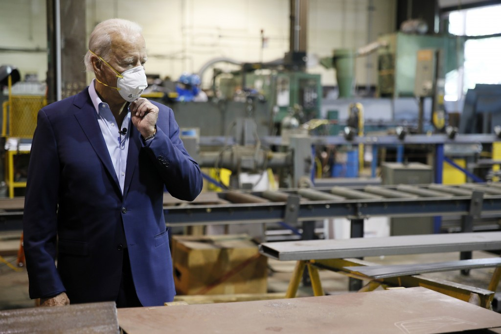 FILE - In this July 9, 2020, file photo Democratic presidential candidate, former Vice President Joe Biden adjusts his mask during a tour of McGregor ...