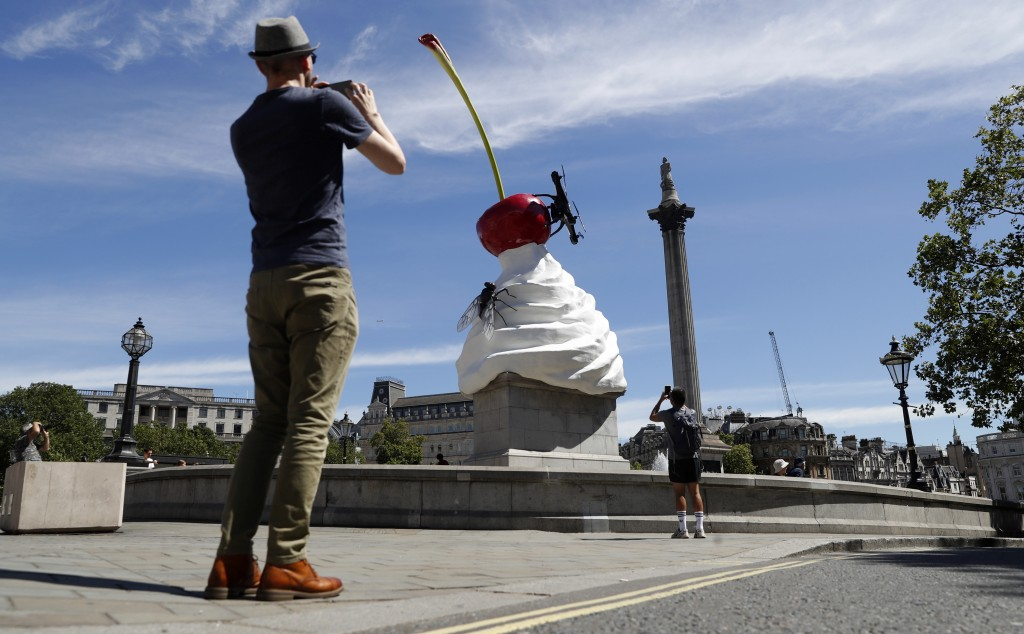 A man takes a smart phone picture of the new work of art entitled 'The End' by artist Heather Phillipson which was unveiled on the fourth plinth in Tr...