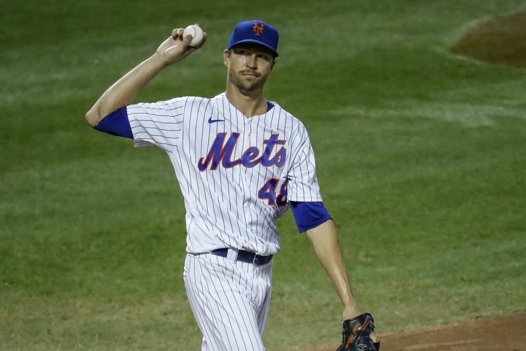New York Mets starting pitcher Jacob deGrom reacts after allowing a run on a wild pitch during the fourth inning of the team's baseball game against t...