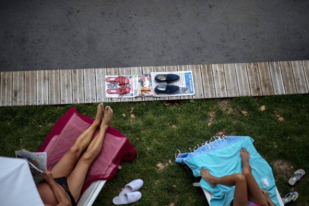 FILE - In this Tuesday, July 28, 2020, file photo, people sunbathe along the river Seine in Paris. An outbreak among 18- to 25-year-olds at a seaside ...