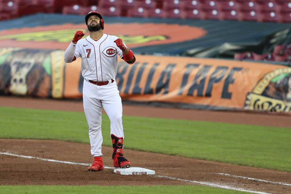 Cincinnati Reds' Eugenio Suarez reacts to hitting a two-run single in the fifth inning of the team's baseball game against the Chicago Cubs in Cincinn...