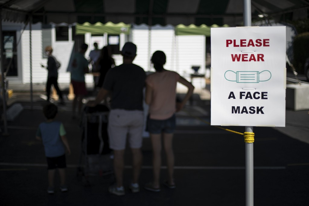 Customers with masks line up at a Brickley's Ice Cream shop, one of two stores, in Narragansett, R.I., Wednesday, July 29, 2020. The other nearby loca...