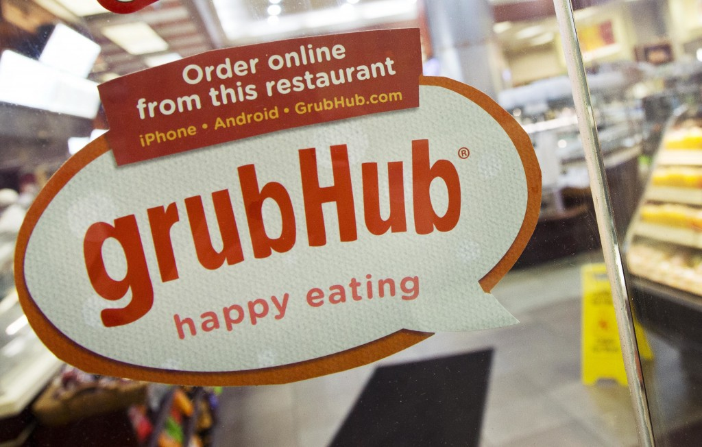 FILE - In this April 4, 2014 file photo, a sign with the old GrubHub logo is displayed is displayed on the door to a New York restaurant.  Grubhub saw...
