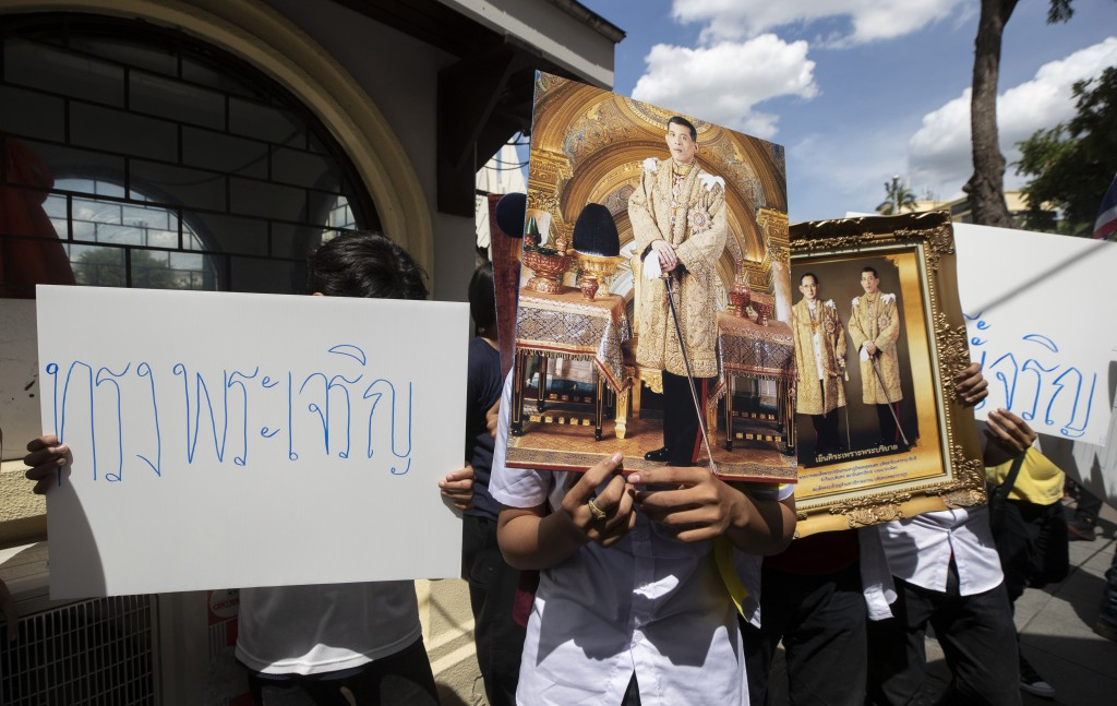 """Supporters of Thailand's monarchy hold posters that read """"long live the King"""" and portraits of Thailand's King Maha Vajiralongkorn and portraits of th..."""