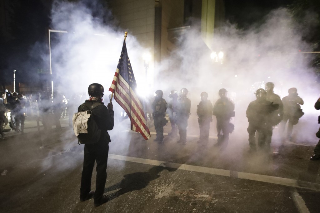 A demonstrator waves a U.S. flags in front of federal agents after tear gas is deployed during a Black Lives Matter protest at the Mark O. Hatfield Un...