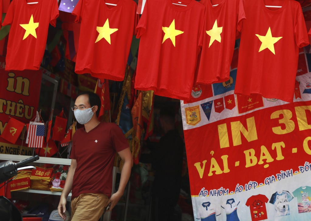 A man walks past a row of T-shirts printed with Vietnamese flags in Hanoi, Vietnam on Thursday, Jul.30, 2020. For 99 days, Vietnam seemed to have defe...