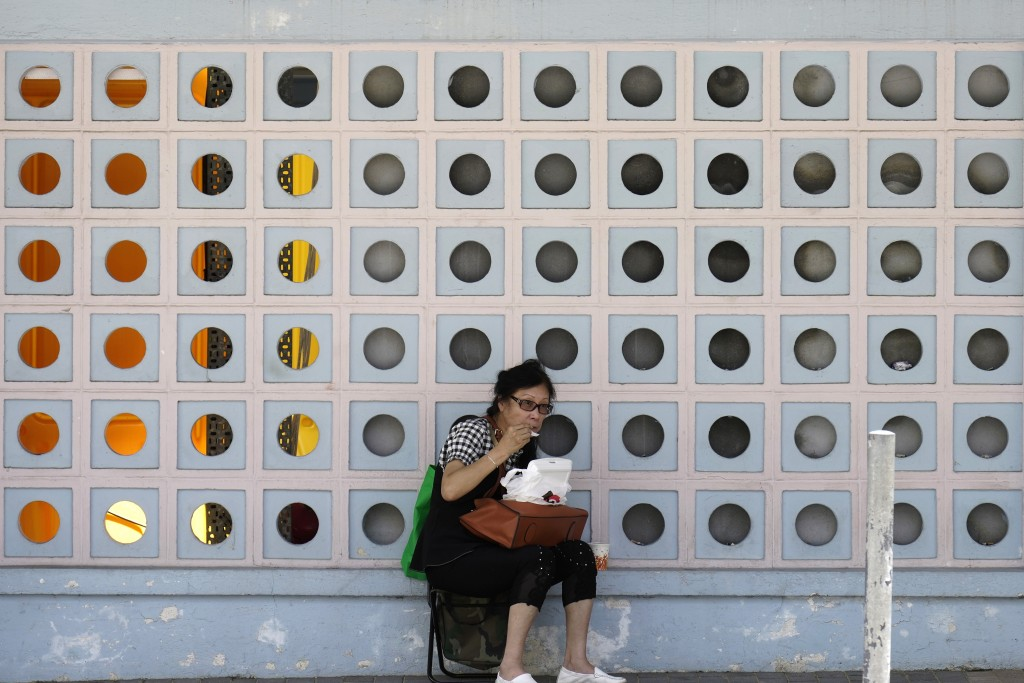 A woman has her lunch on a sidewalk in Hong Kong, Thursday, July 30, 2020. Hong Kong's government on Thursday reversed its decision to impose a total ...