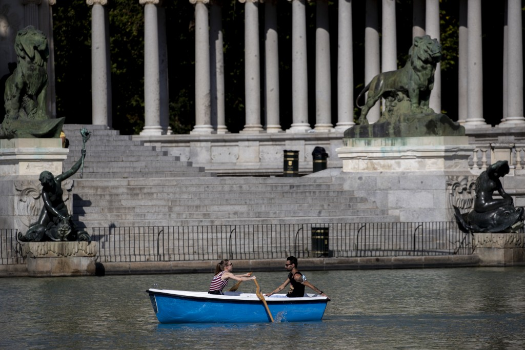 A couple sail a boat during a hot day of summer at the Retiro park in Madrid, Spain, Wednesday, July 29, 2020. The first heat wave of the summer, whic...
